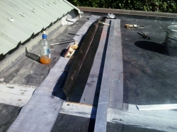 the upper edge is peeled back and cleaned, primed, then eased down onto the seam tape of the new strip of EPDM
