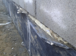 junction between footing and concrete block wall, some loose footing membrane