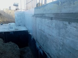 east end footing slab and cast concrete wall, partially coated with hydroepoxy primer