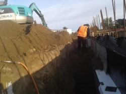 contractor compacting sand backfill in trench